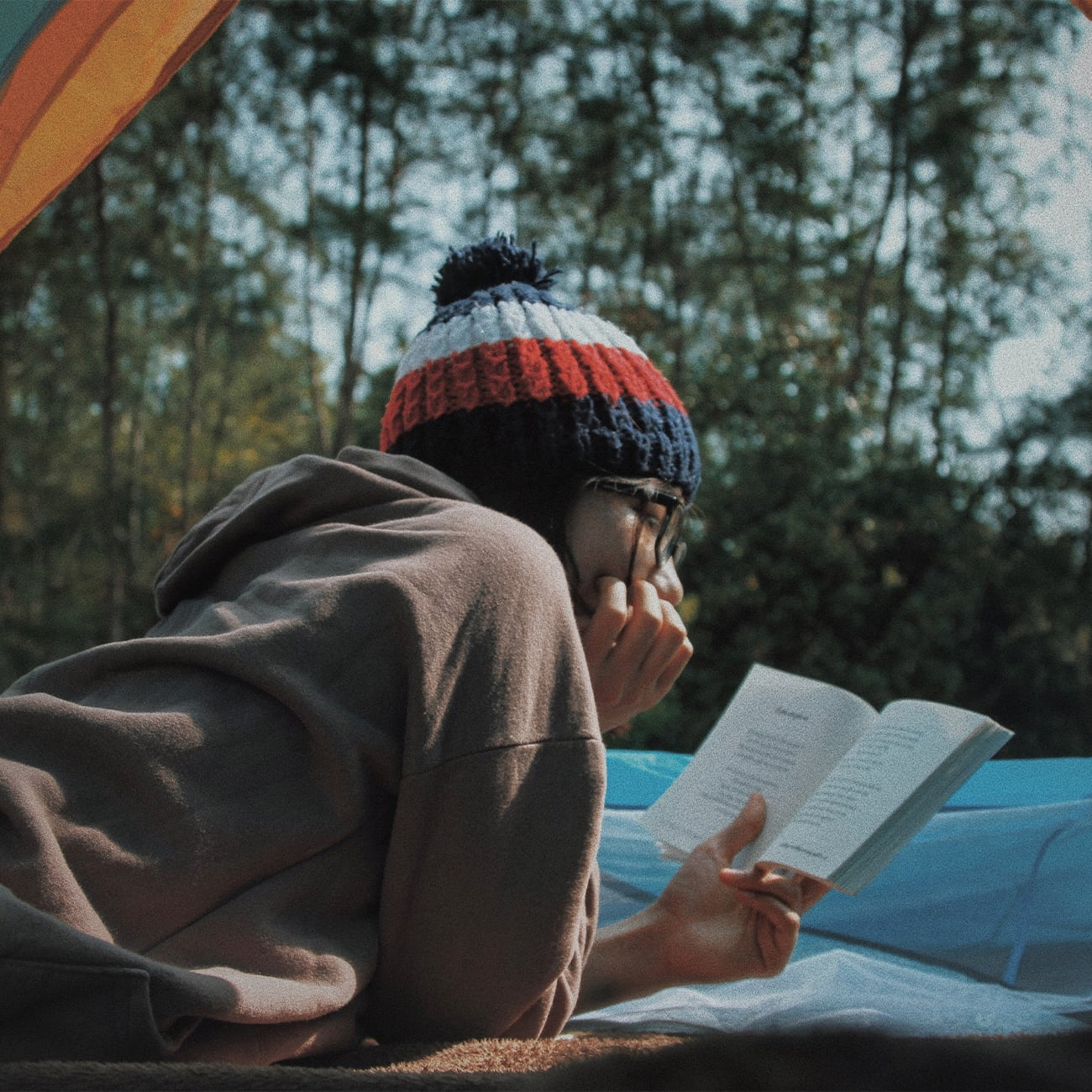 Woman reading book from inside tent