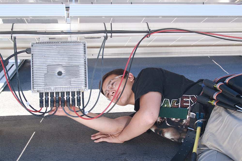 Male student wiring solar panel